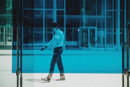 Anonymous elegant businessman walking on street and talking on smartphone