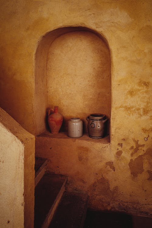 Various pots decorating ancient house with aged steps