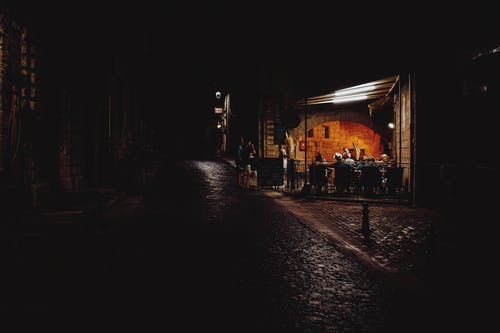 Anonymous travelers resting in cafe in aged town at night