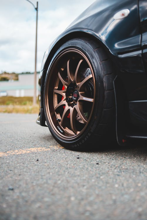 Big wheel of car parked on paved road