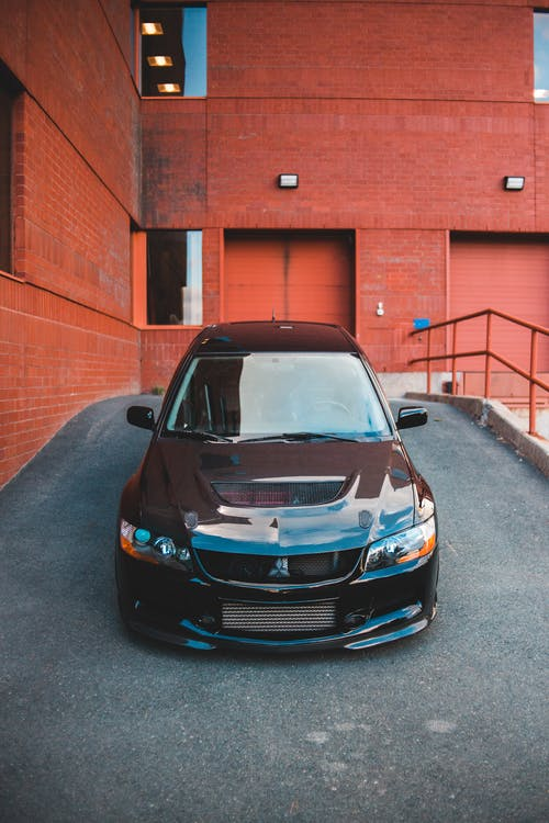 Modern black automobile with body kit parked on asphalt ramp near residential house with brick walls in city street in