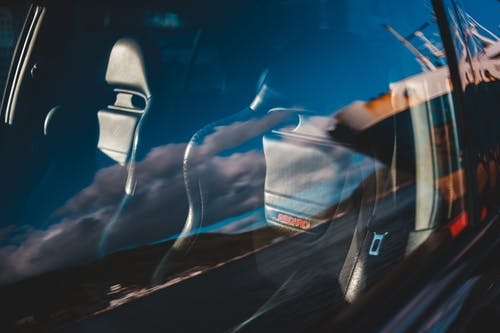 Car cabin behind window with reflection of sky