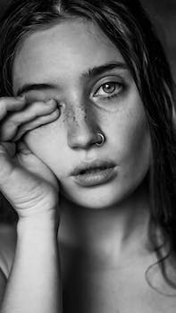 young sad female with freckles and piercing