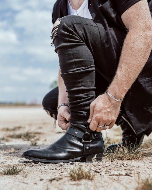 Мужчина в черной кожаной куртке и черных джинсовых джинсах сидит на земле