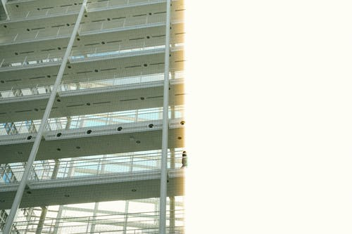 From below of multi storey construction with metal beams inside modern office building in sunny daylight
