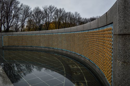Memorial wall decorated with golden stars in park on rainy day