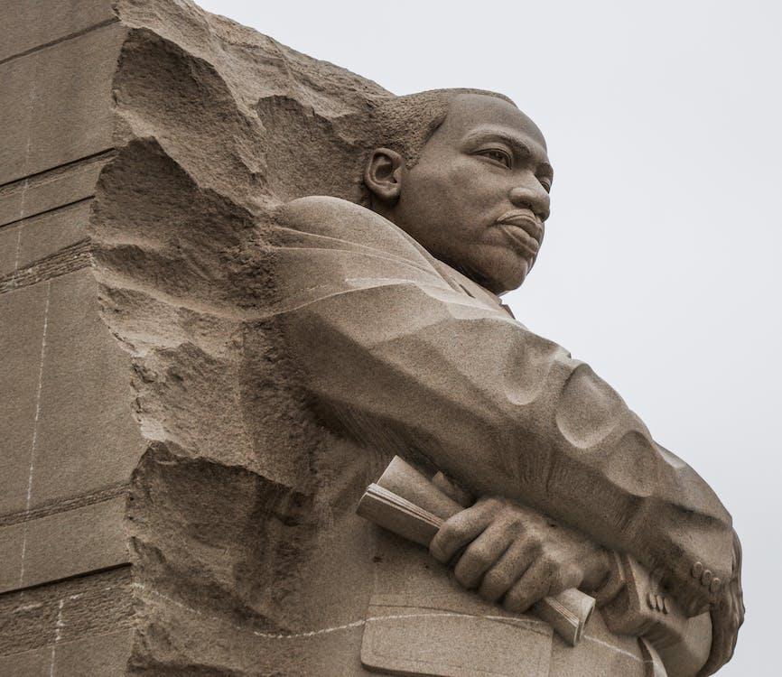 Granite statue of civil rights movement leader against overcast sky