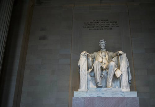 From below of marble statue of American president sitting on chair near wall with inscription located in Washington DC
