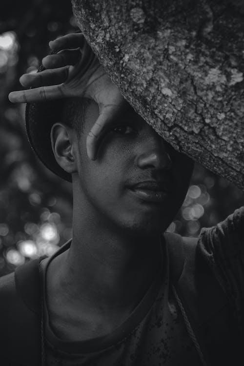 Serious black man behind tree trunk