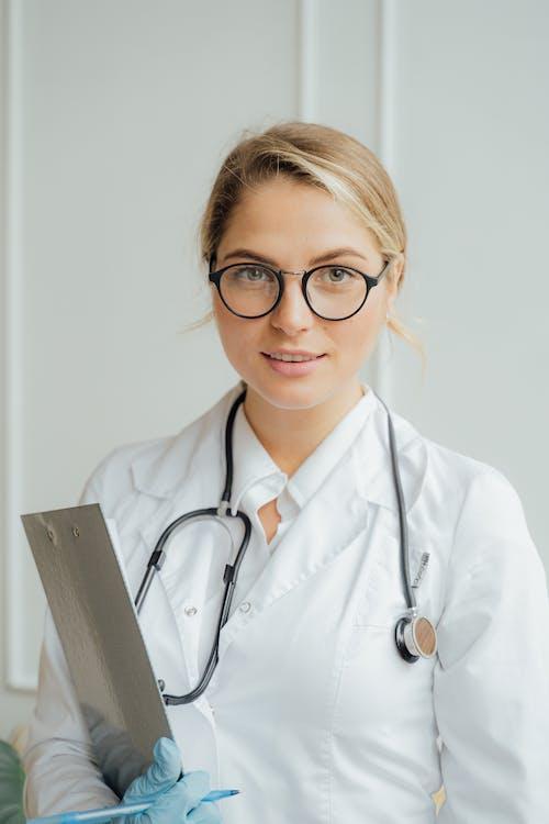 Woman in White Scrub Suit Holding Gray Rectangular Frame