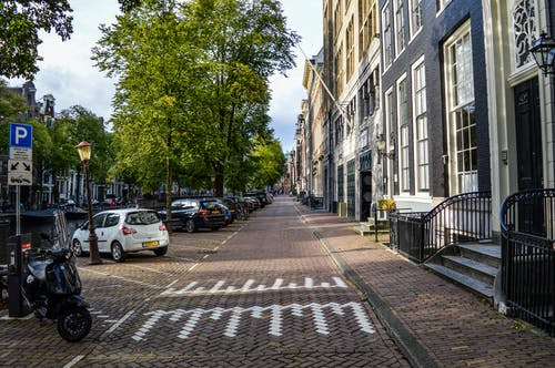 Empty paved bicycle road and sidewalk between aged residential buildings and canal in sunny morning in Amsterdam