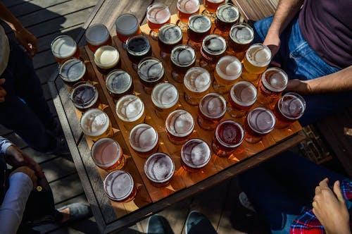 Unrecognizable people tasting different varieties of beer in cafe