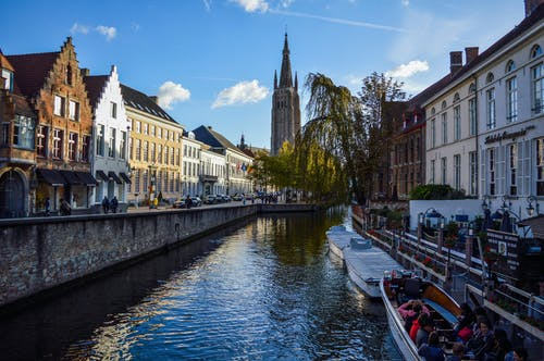 Picturesque scenery of rippling canal flowing near aged typical houses and historical Church of Our Lady against blue sky in Bruges