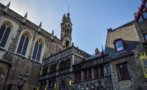 From below exterior of medieval Basilica of the Holy Blood with amazing ornamental design and tower against cloudless blue sky in Bruges
