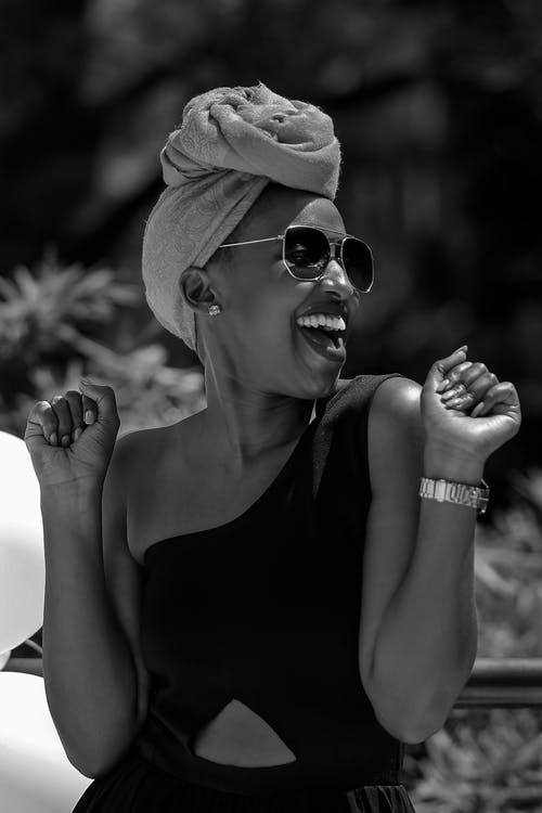 Black and white glad young African American female with mouth opened wearing trendy sunglasses turban and dress smiling happily