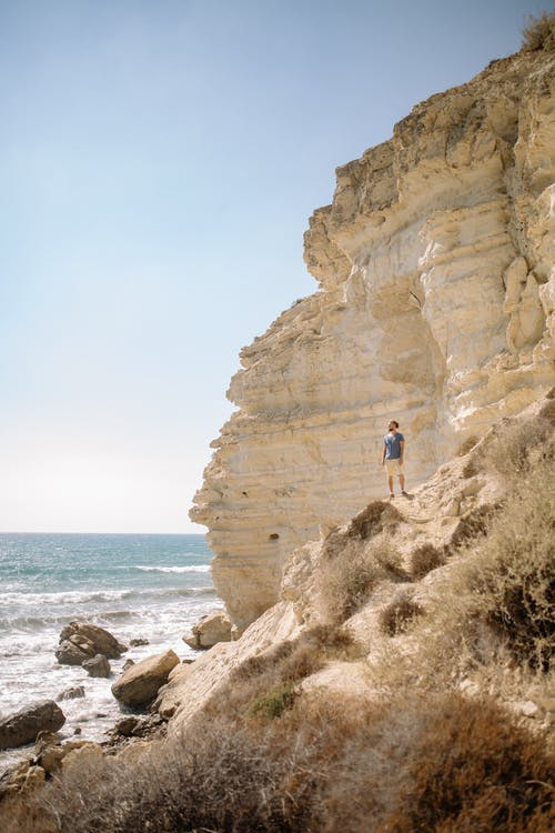 Man Standing on Brown Rock Formation