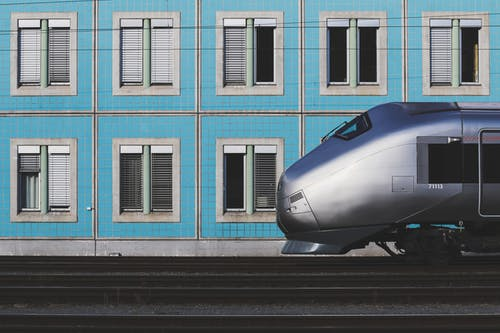 Gray Train Passing By near Blue Wall
