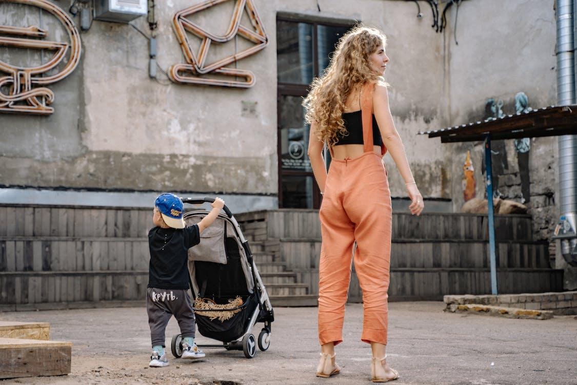 Woman in Orange Pants Standing beside a Boy Holding Stroller