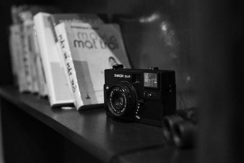 Small analog camera on wooden shelf