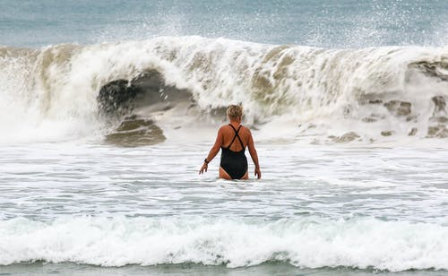 Woman in Black Swimsuit Standing on Beach with Big Waves