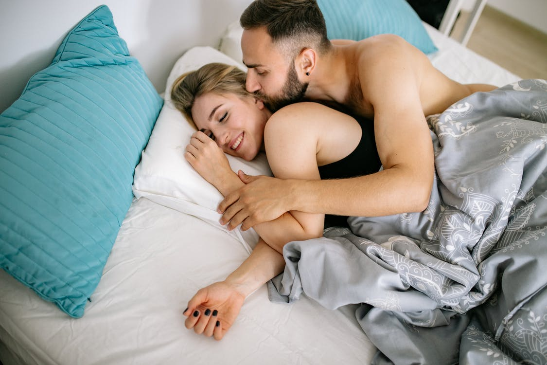 Shirtless Man Kissing a Woman while Lying on Bed