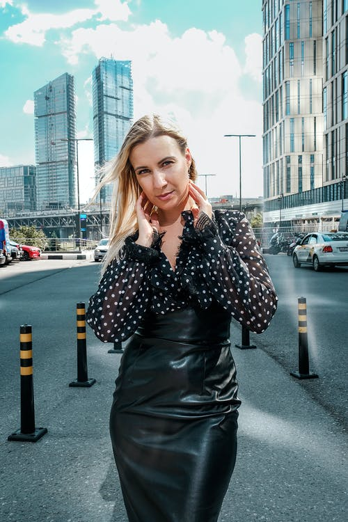 Trendy woman standing on busy urban road and touching face