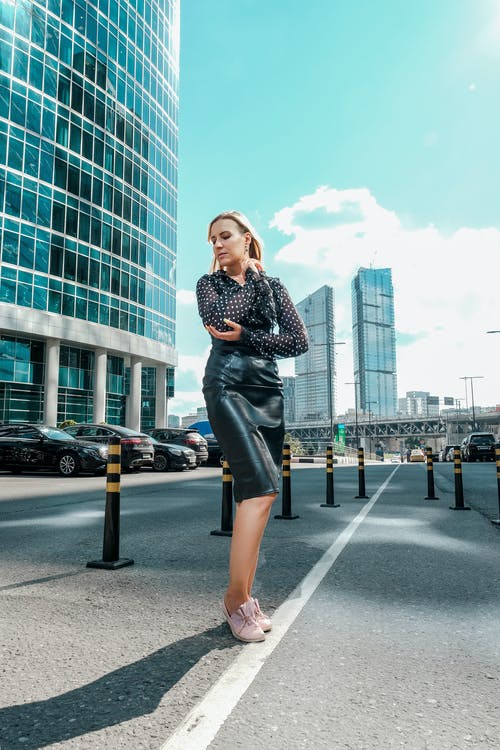 Full length graceful young female in trendy leather skirt standing against contemporary skyscrapers and looking down
