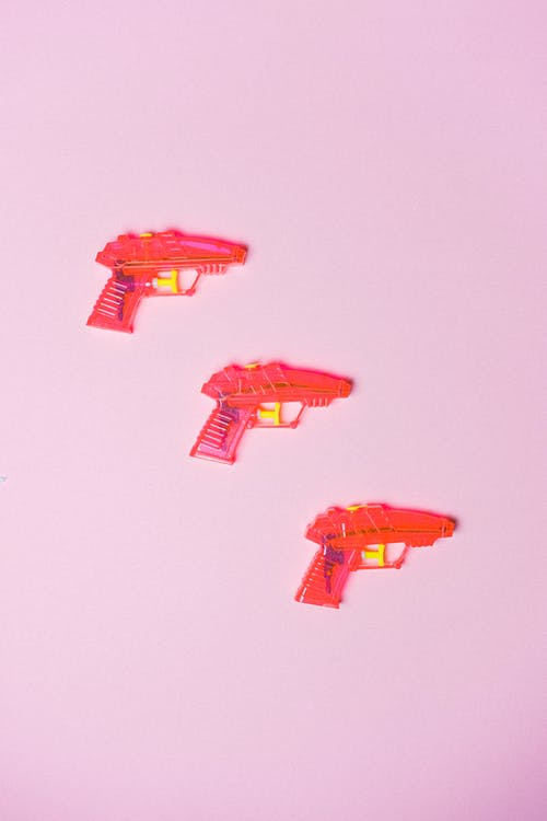 Top view of composed miniatures of guns for playing games on pink background