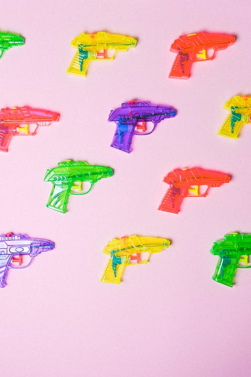 Colorful guns in rows on pink surface