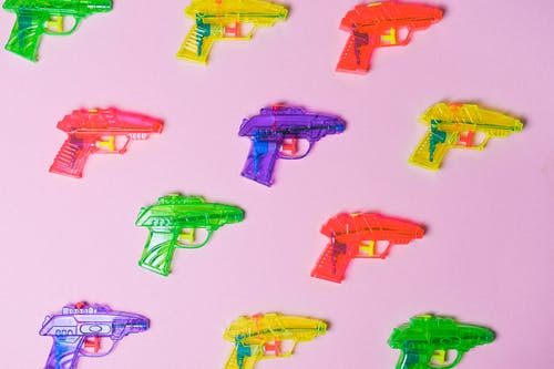 Top view of various multicolored toys for fight arranged on pink background as representation of game