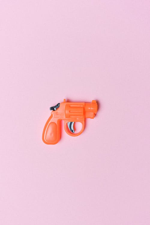 Red revolver for game on pink background