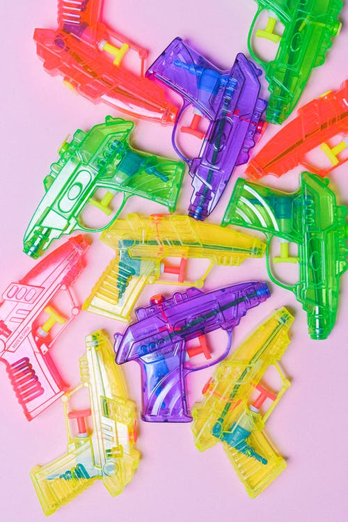 Colored pistols made of plastic on pink background