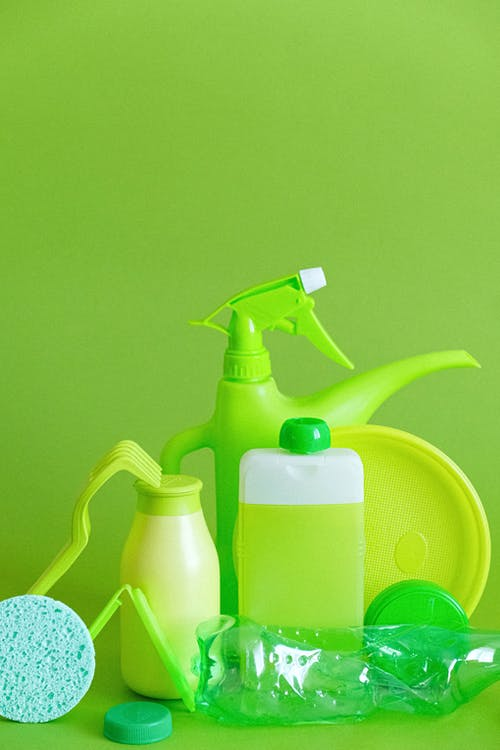 Green detergent bottle with sprayer and sponge with plate