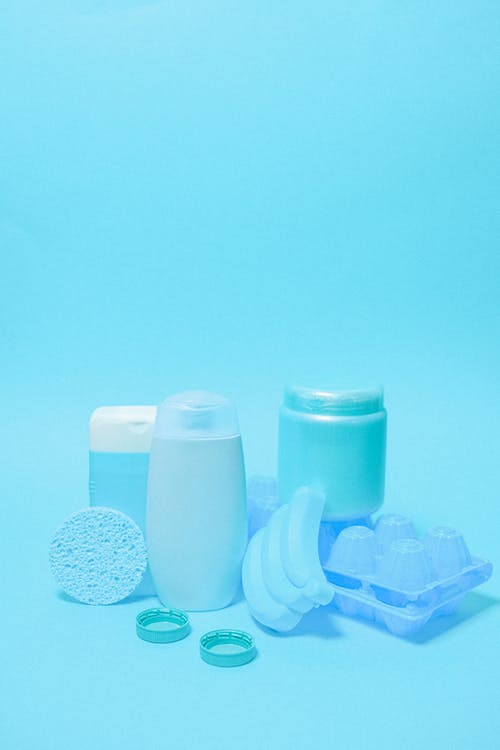 Collection of various products in plastic bottles placed with sponge lids and egg tray on blue background