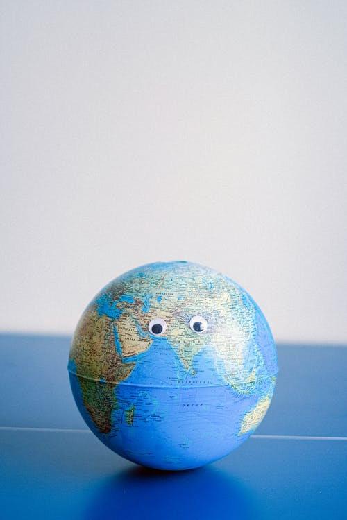 Sphere shaped miniature of Earth with googly eyes