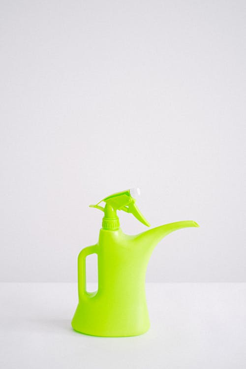 Green plastic reusable bottle for liquid intended for watering and spraying plants on white background