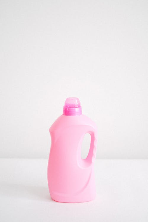 Plastic bottle of fabric softener chemical liquid for washing and household chores against white background