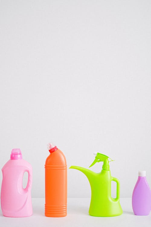 Collection of colorful bottles of detergent and cleaning supplies placed in row on table against white background in light room