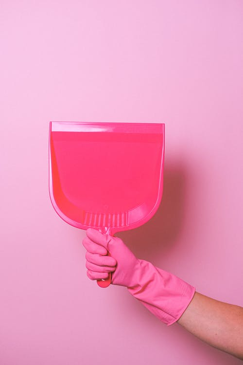 Crop anonymous person in pink rubber glove showing pink plastic dust shovel in light studio