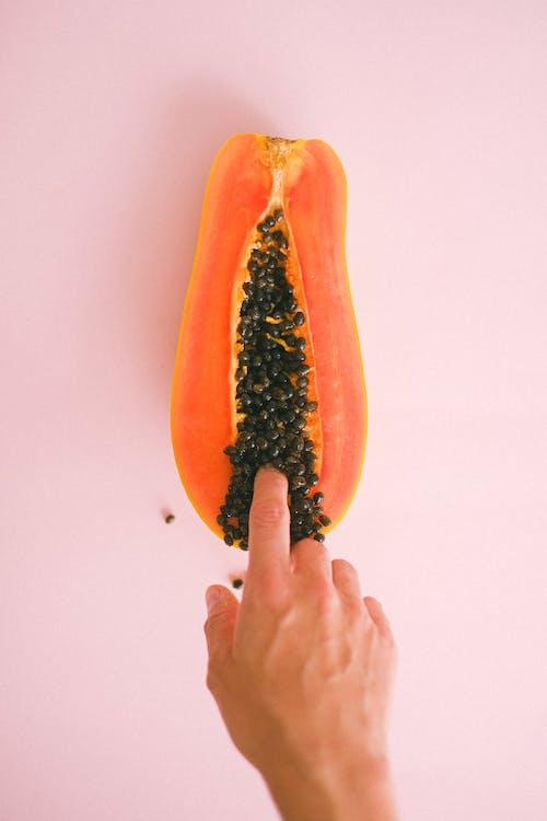 Crop faceless woman touching cut sweet papaya