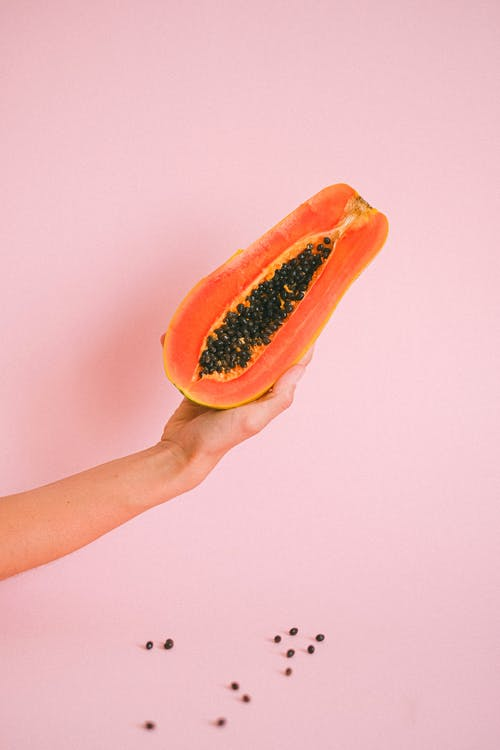 Crop faceless woman demonstrating half papaya fruit