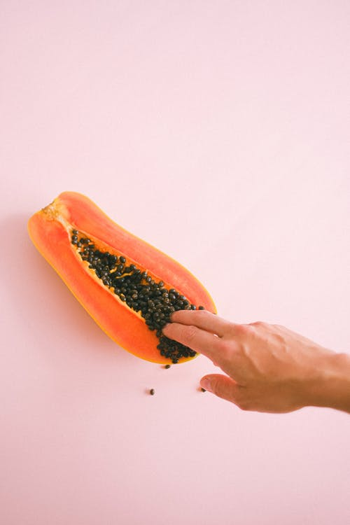 Crop unrecognizable woman touching ripe cut papaya