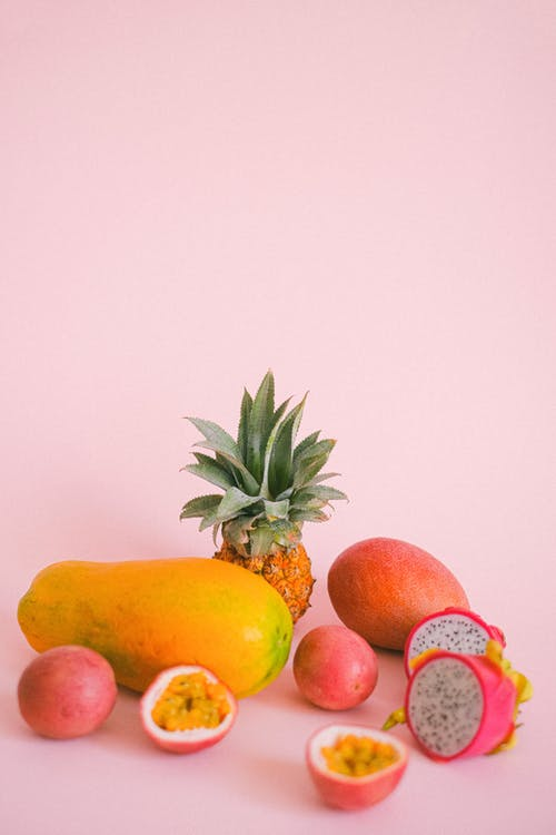 Assorted exotic fruits on pink background