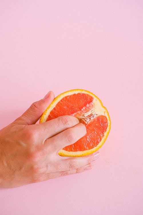 Person Holding Sliced Orange Fruit