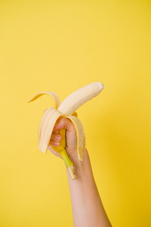 Crop anonymous female holding half unpeeled ripe organic banana against bright yellow background before eating