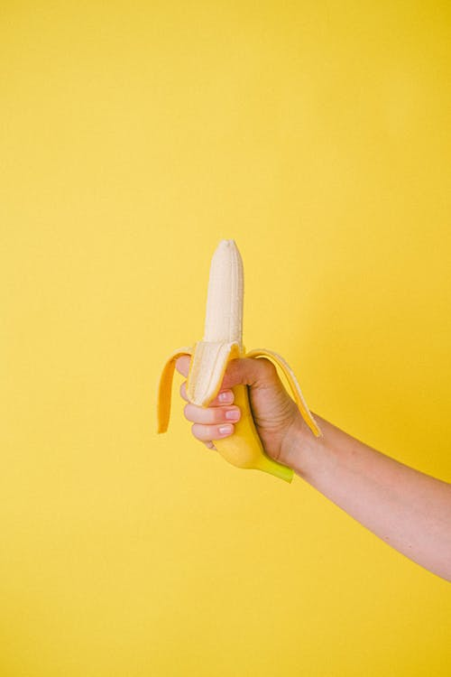 Crop anonymous female showing sweet half unpeeled banana against bright yellow wall in studio