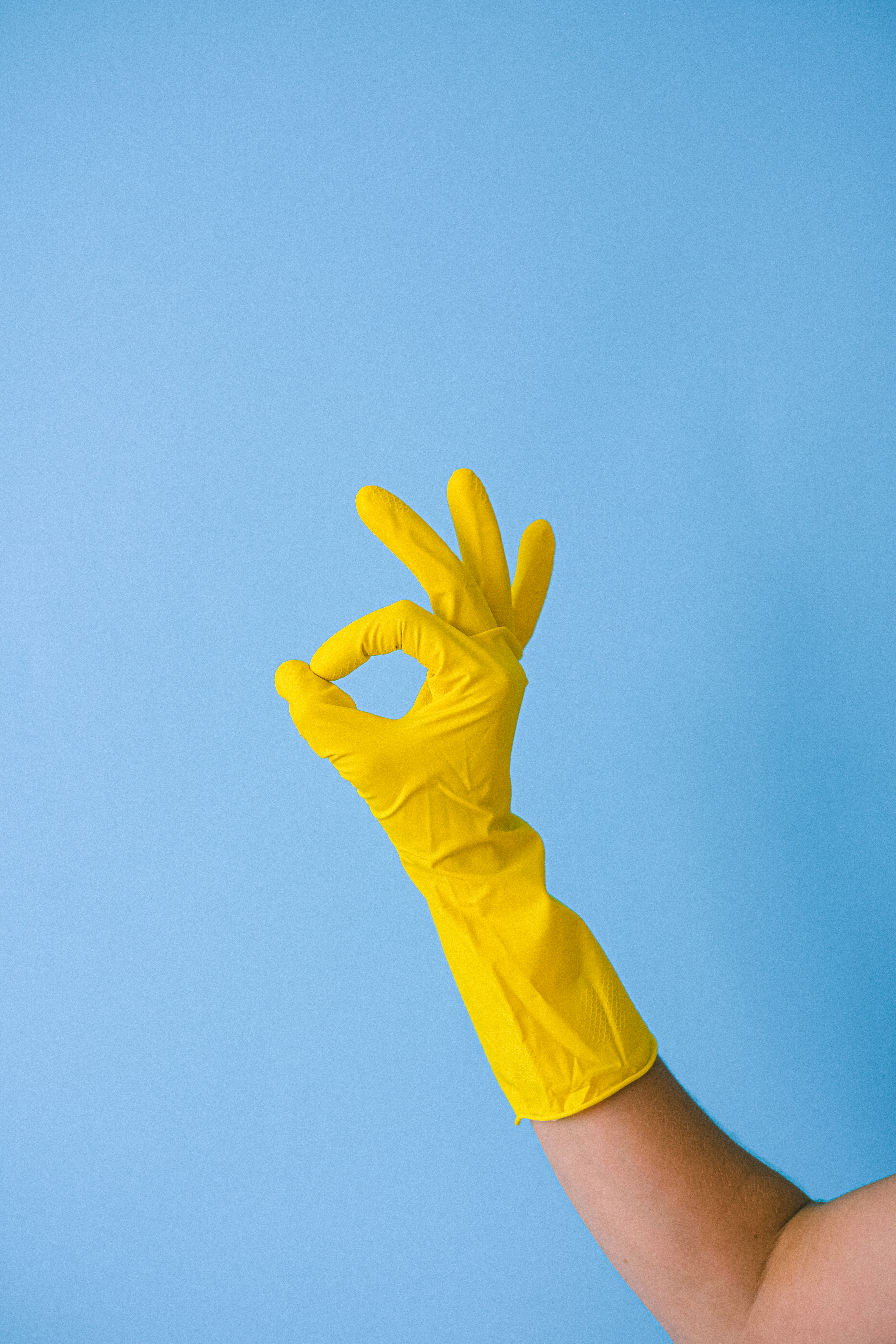 crop faceless person in rubber glove showing okay gesture