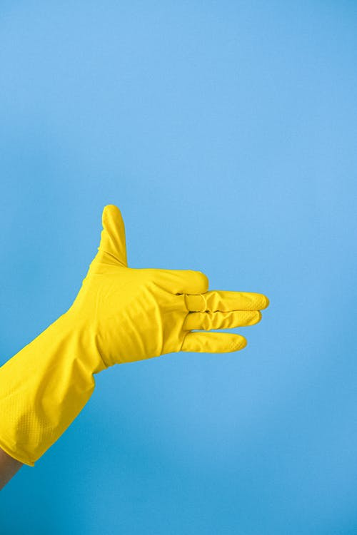 Crop anonymous person in yellow latex glove demonstrating finger gun gesture against blue wall