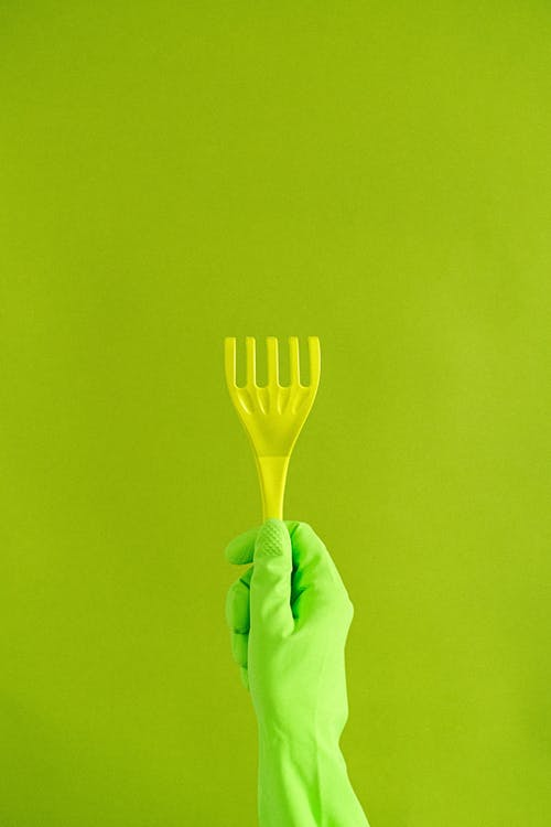 Crop anonymous person in protective gloves demonstrating plastic supply for household needs on green background