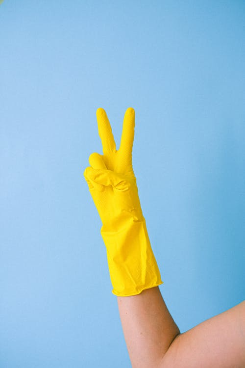 Crop hand of anonymous person in rubber gloves for cleaning demonstrating peace symbol against blue background